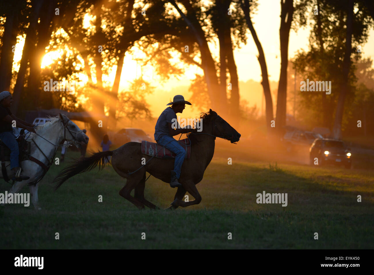 Pine Ridge Reservation, South Dakota, US. 30th July, 2015. Two young Lakota riders, run their ponies across the Stock Photo