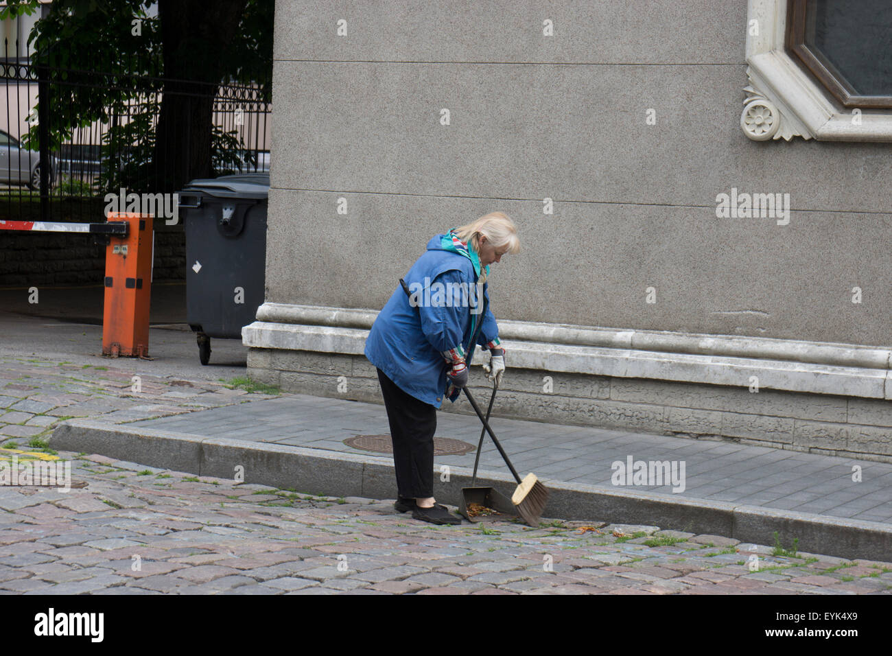 A woman sweeping the street early one morning in Tallinn, Estonia's old town. - Stock Image