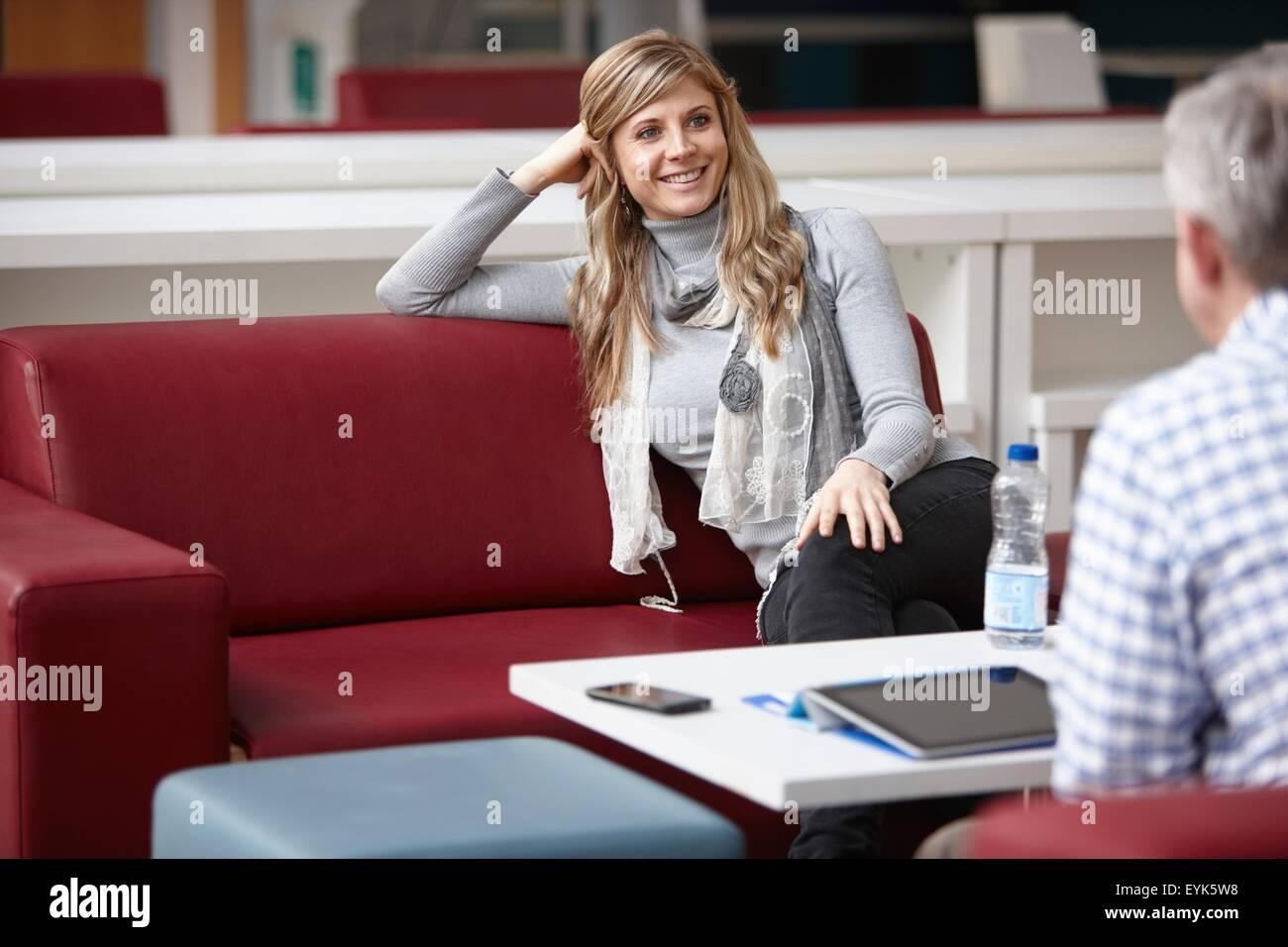 Businessman and woman meeting on office sofas - Stock Image