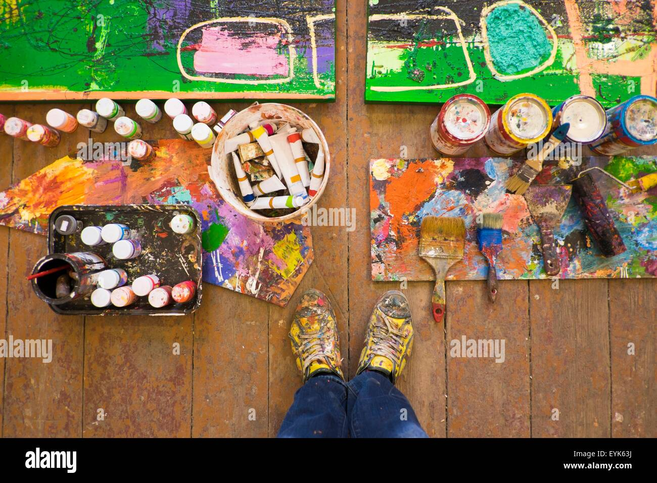 Artist selfie of feet paints and abstract painting in studio - Stock Image
