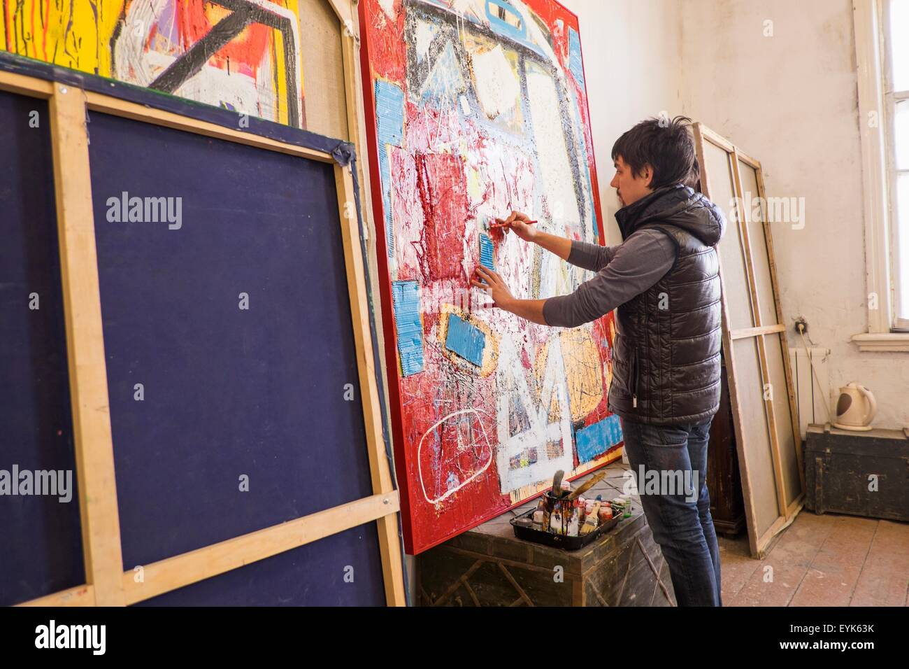 Artist drawing on abstract painting in studio - Stock Image