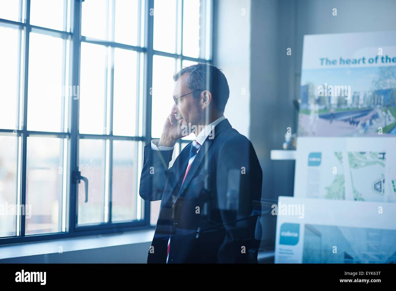Business man chatting on smartphone whilst looking out of office window Stock Photo