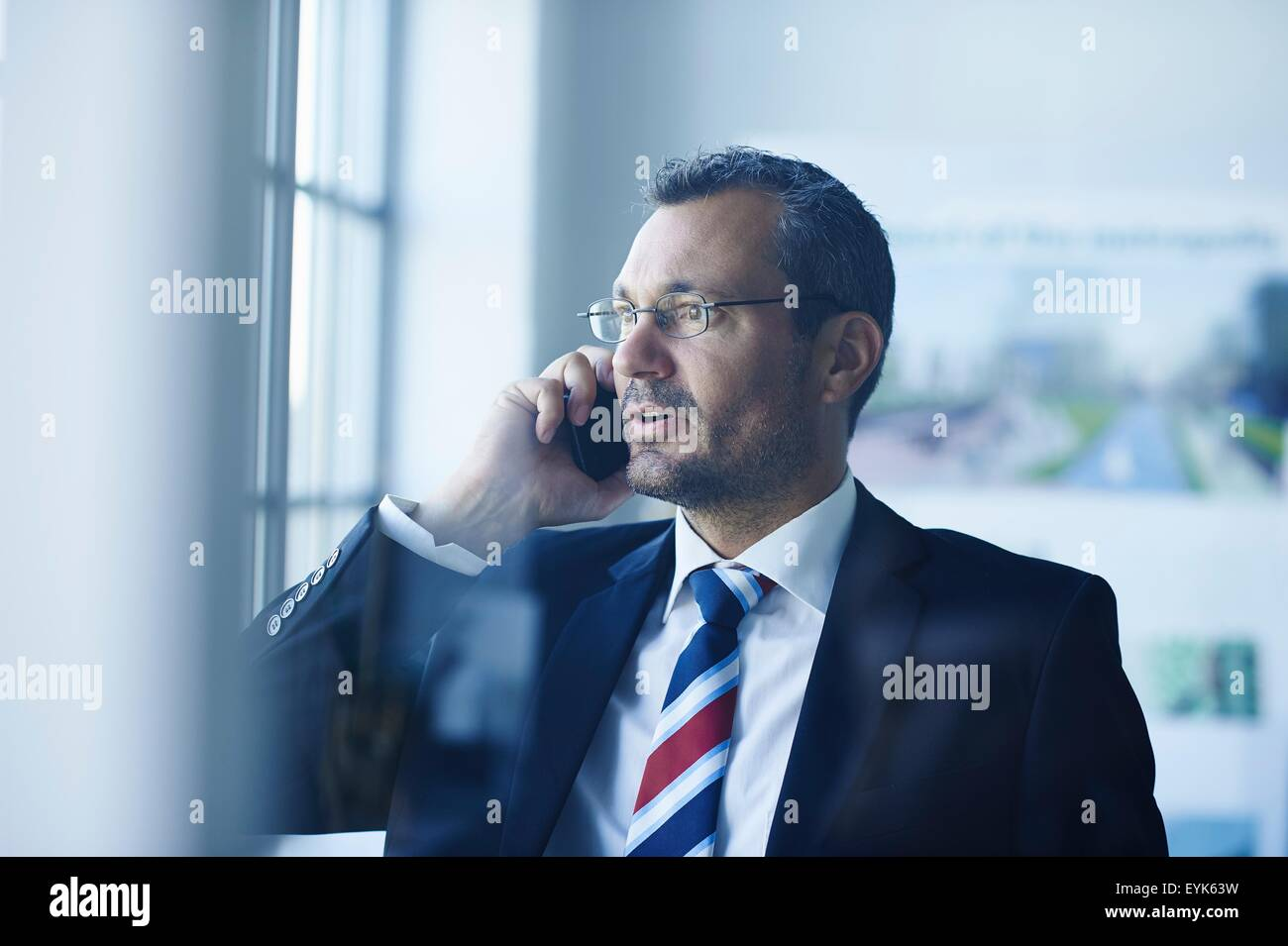 Business man chatting on smartphone whilst looking out of window Stock Photo