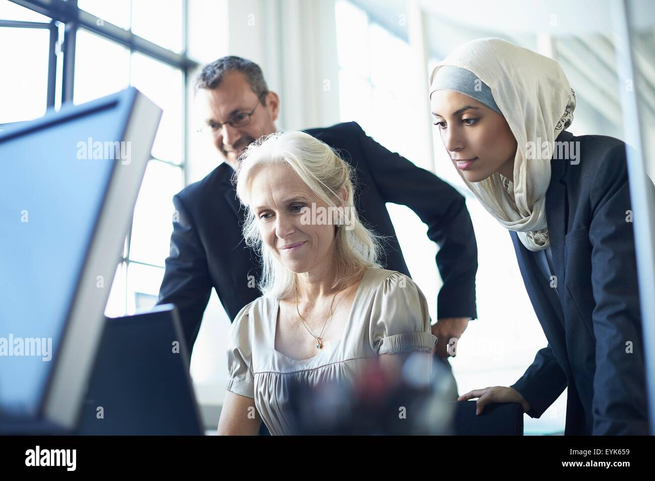 Business team looking at personal computer at office desk - Stock Image