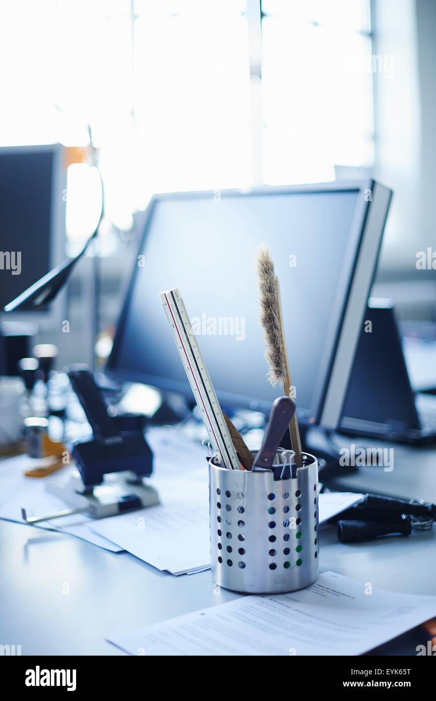 Desk tidy and personal computer on office desk - Stock Image