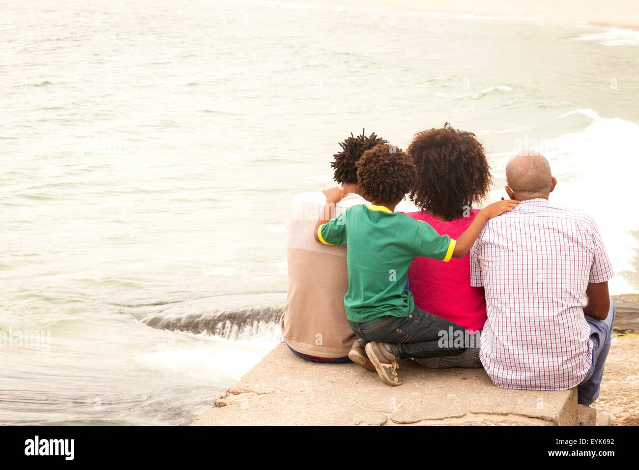 Rear view of mature man and family looking out to sea on Ipanema Beach, Rio De Janeiro, Brazil - Stock Image