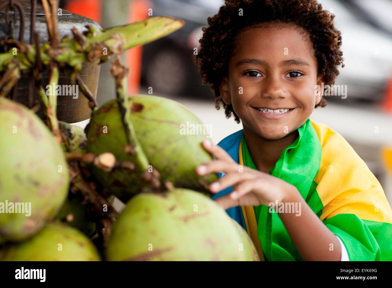 Portrait of boy wrapped in Brazilian flag selecting coconut on Ipanema beach, Rio De Janeiro, Brazil - Stock Image