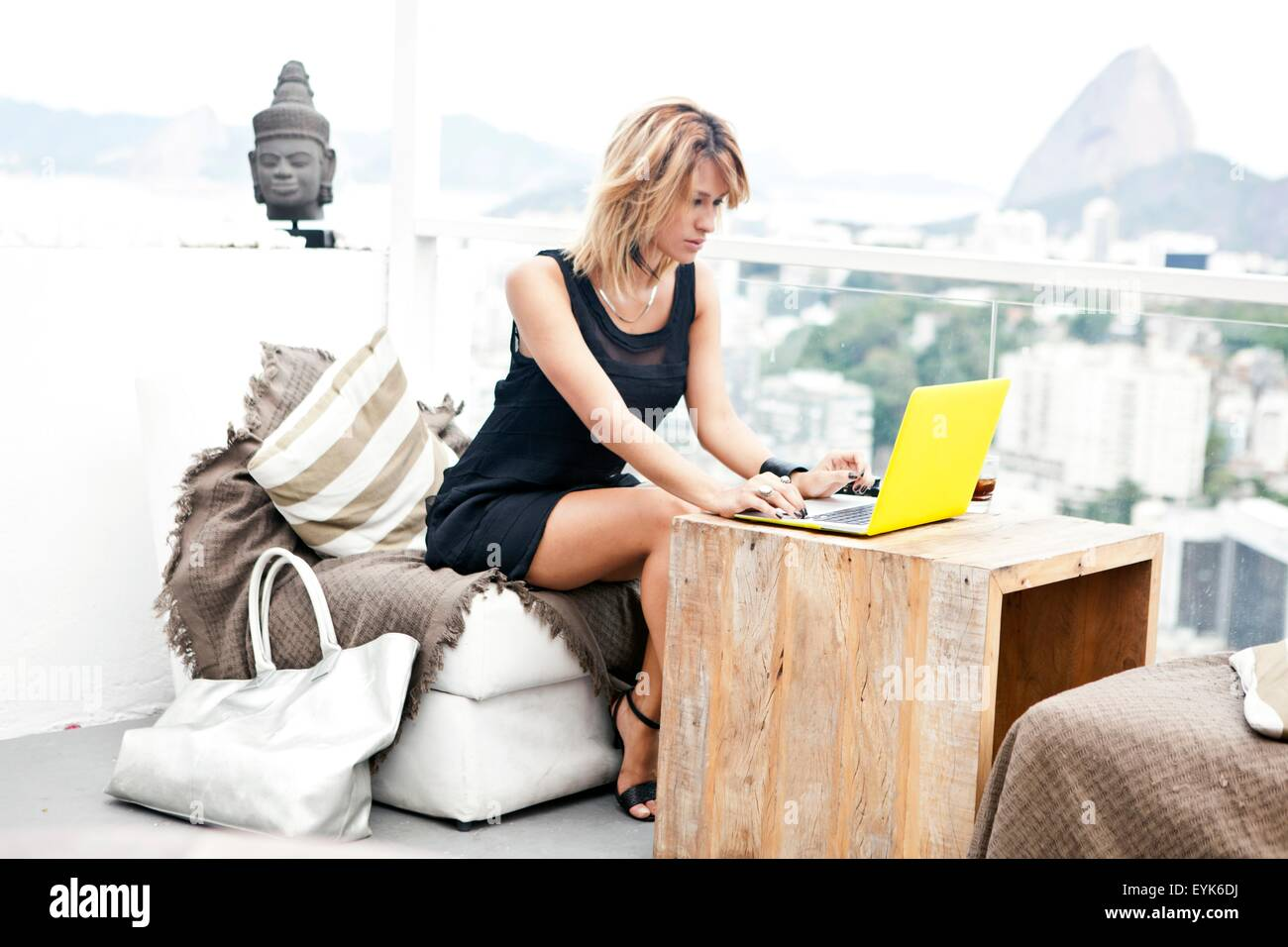 Young woman typing on laptop on rooftop terrace, Rio De Janeiro, Brazil - Stock Image