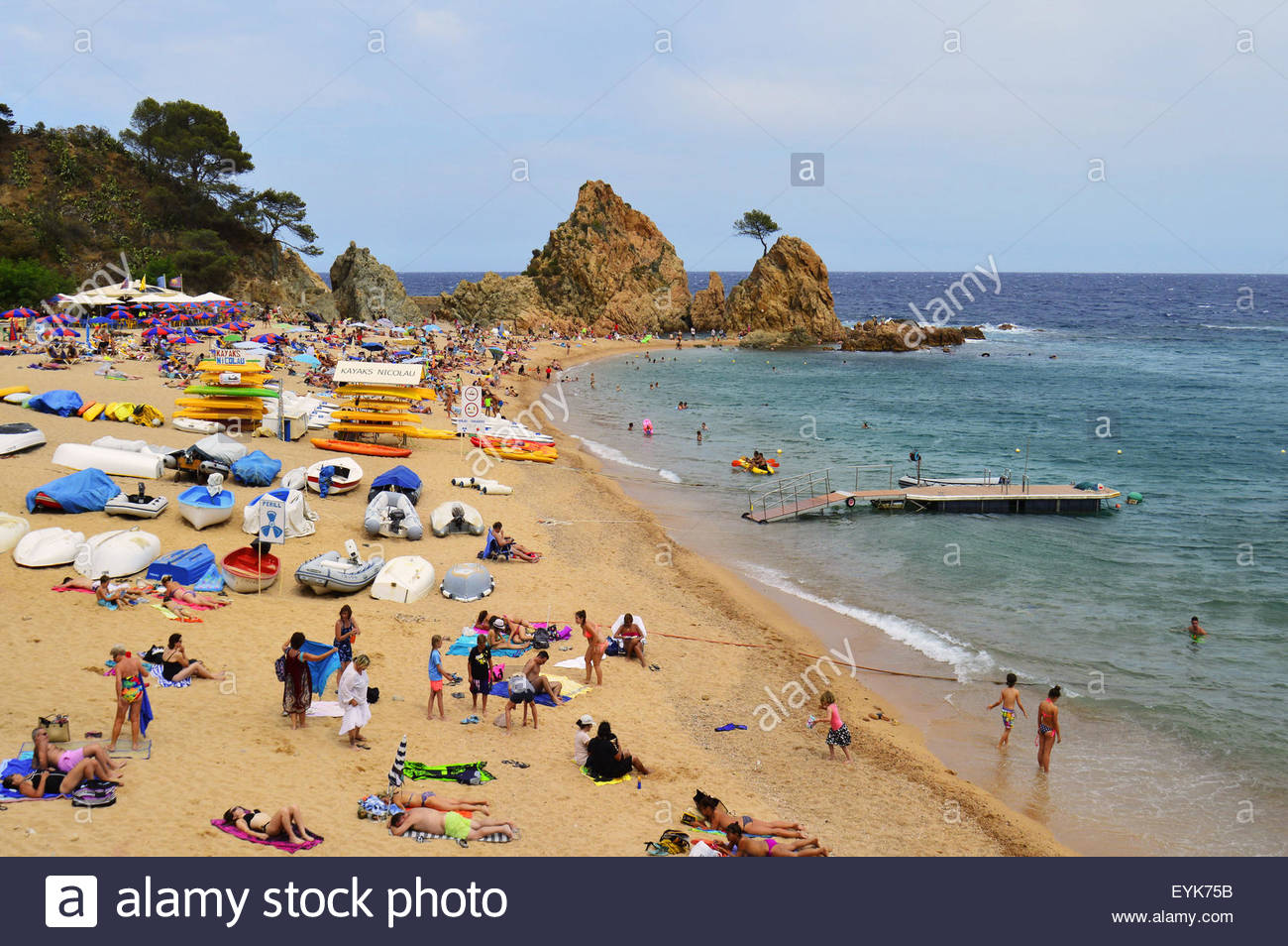 Holidaymakers on the beach of Tossa de Mar Costa Brava Catalonia Spain Europe - Stock Image