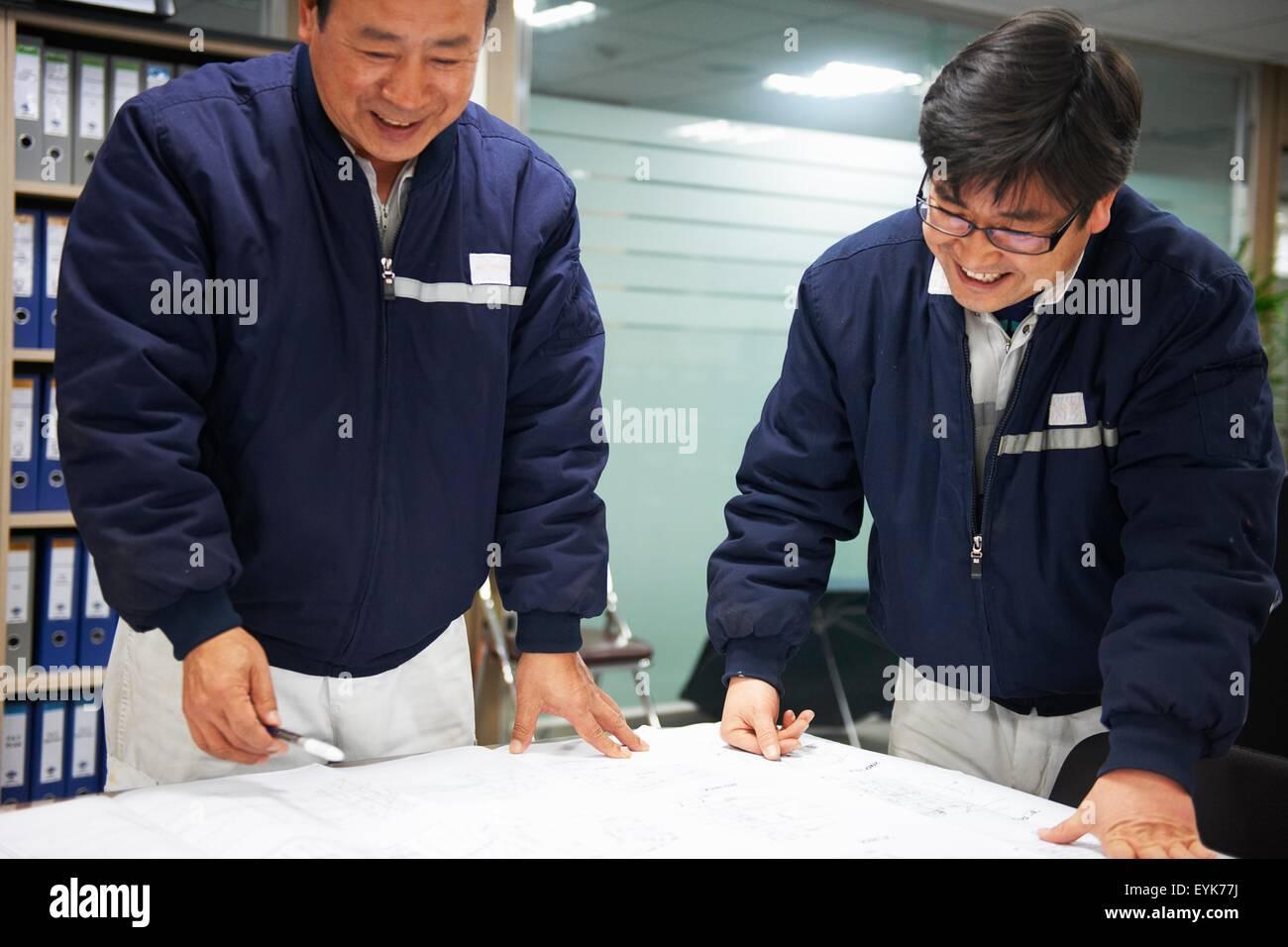 Workers looking at ship plans, GoSeong-gun, South Korea - Stock Image