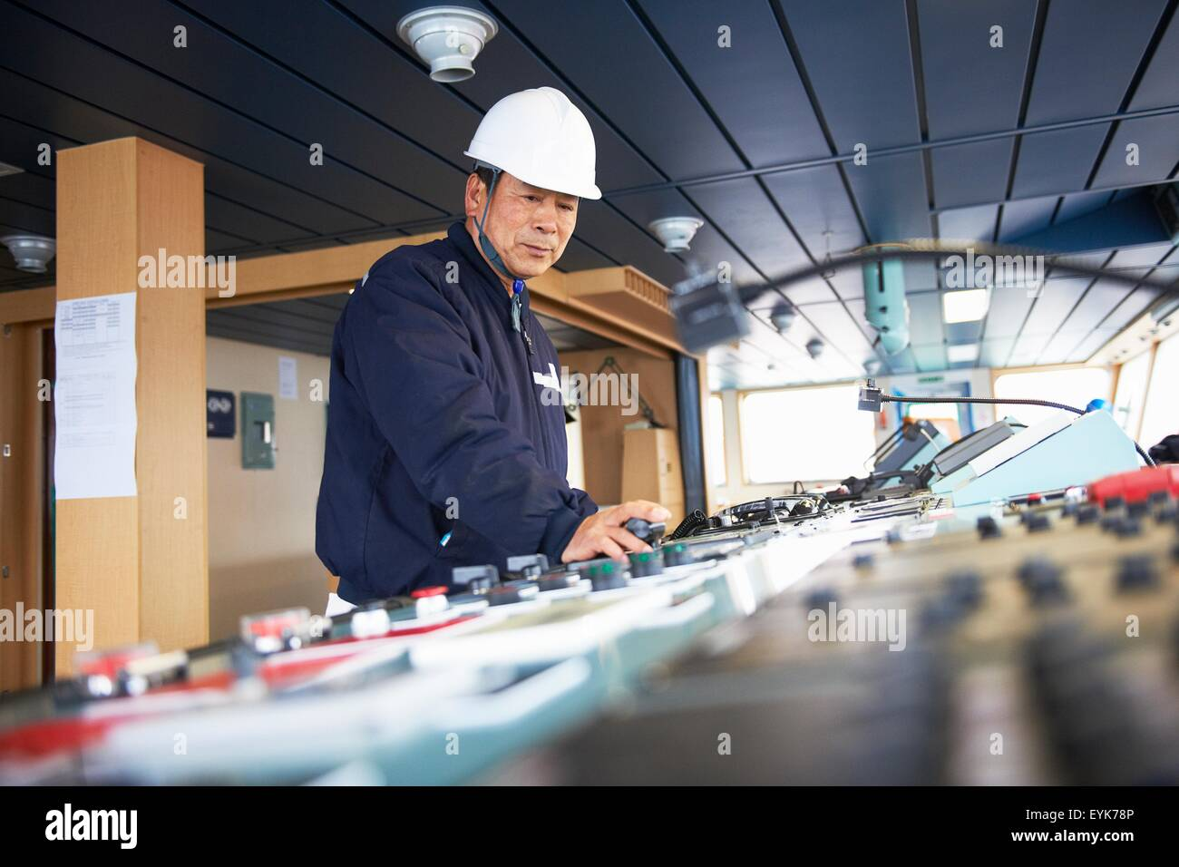 Worker using equipment at shipping port, GoSeong-gun, South Korea - Stock Image