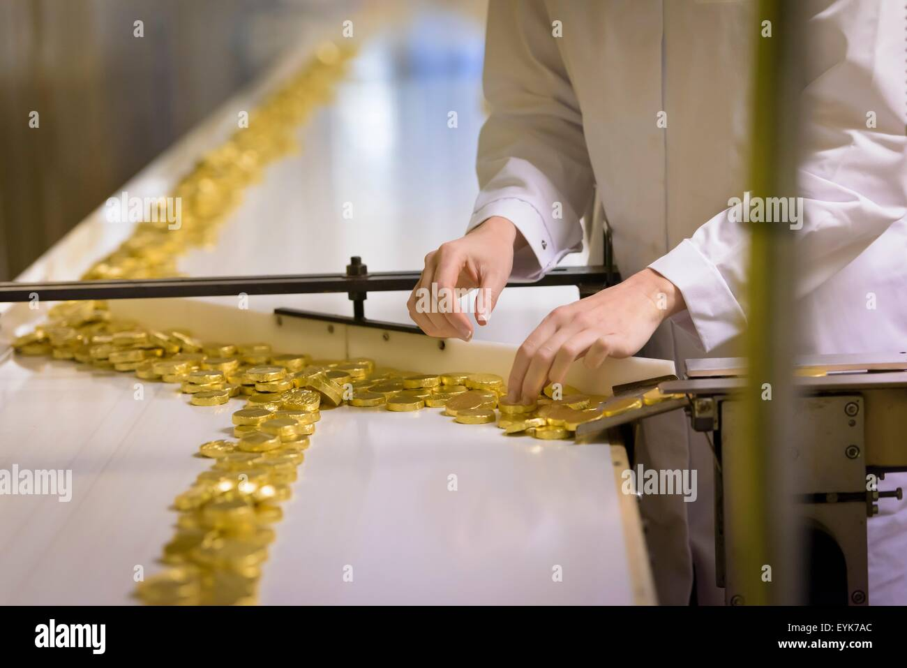 Worker wrapping chocolates on production line in chocolate factory - Stock Image