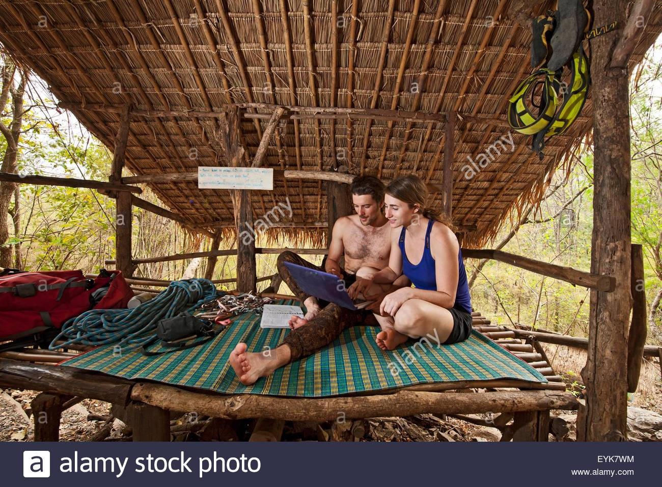 Couple looking at laptop at the Crazy Horse Buttress climbing area, Chiang Mai, Thailand - Stock Image