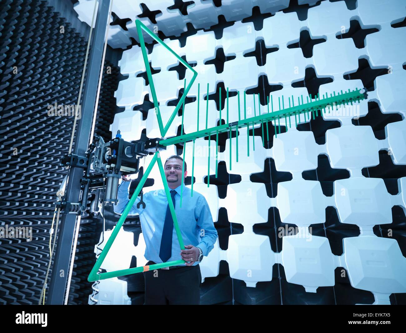 Engineer checking a bilog antenna's height for electromagnetic compatibility (EMC) radiated immunity testing - Stock Image