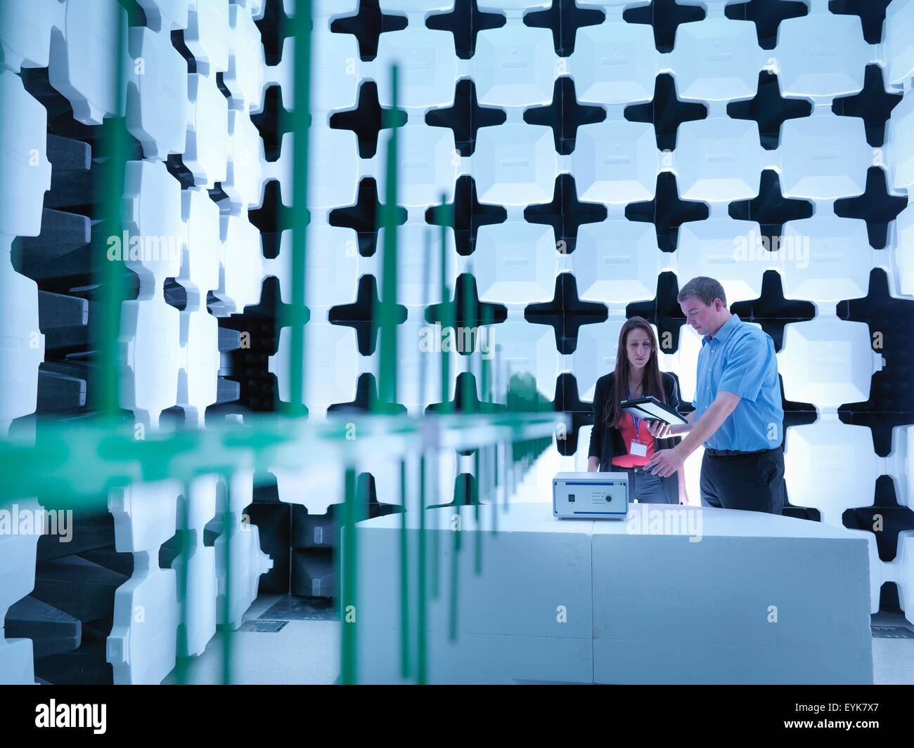 Engineers checking the equipment under test (EUT), in a semi anechoic chamber with energy absorbers and bilog antenna - Stock Image