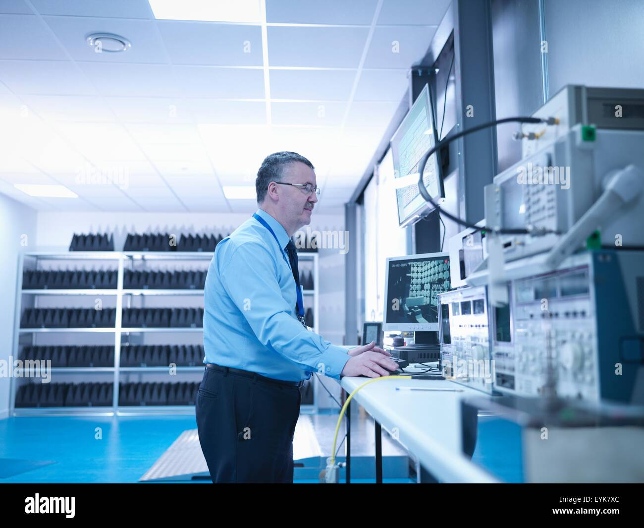 Electromagnetic compatibility engineer carrying out radiated emissions scan on electrical equipment in anechoic - Stock Image