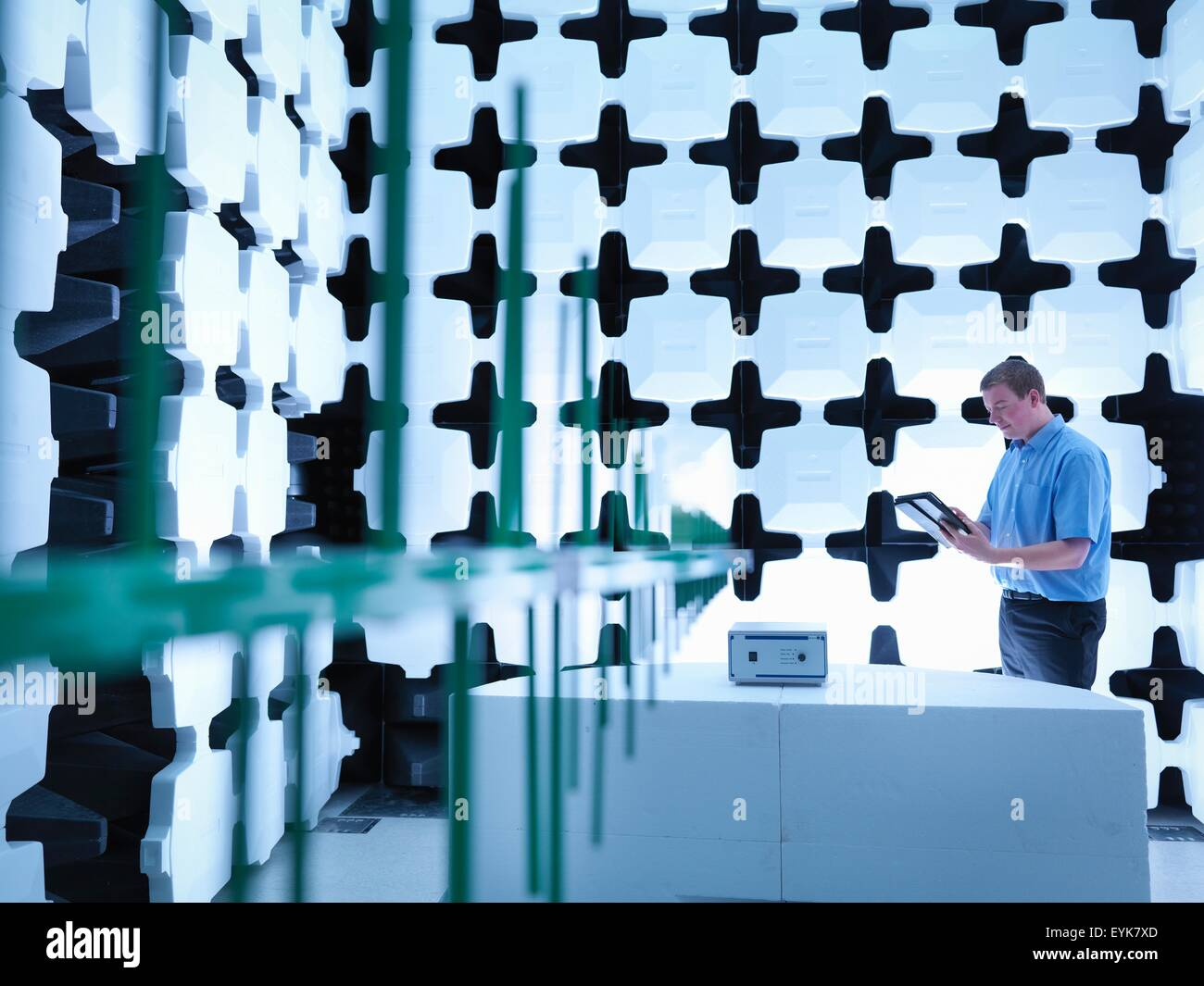Engineer checking the equipment under test (EUT), in a semi anechoic chamber with energy absorbers and bilog antenna - Stock Image