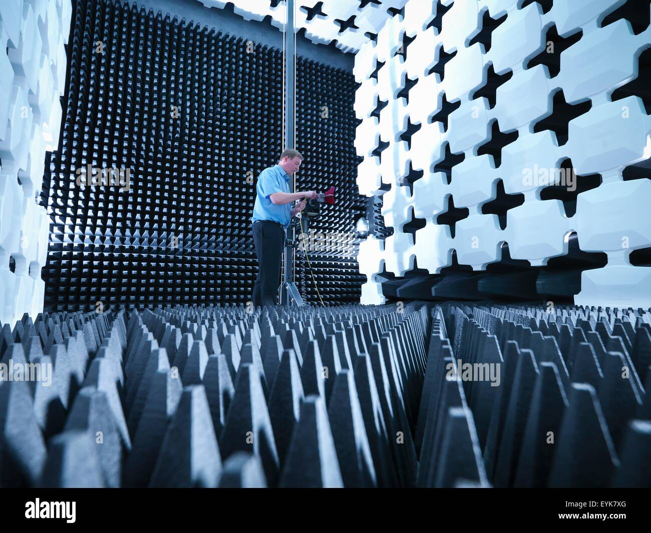 Engineer in anechoic chamber with horn antenna set up for Electromagnetic compatibility (EMC) radiated emission - Stock Image