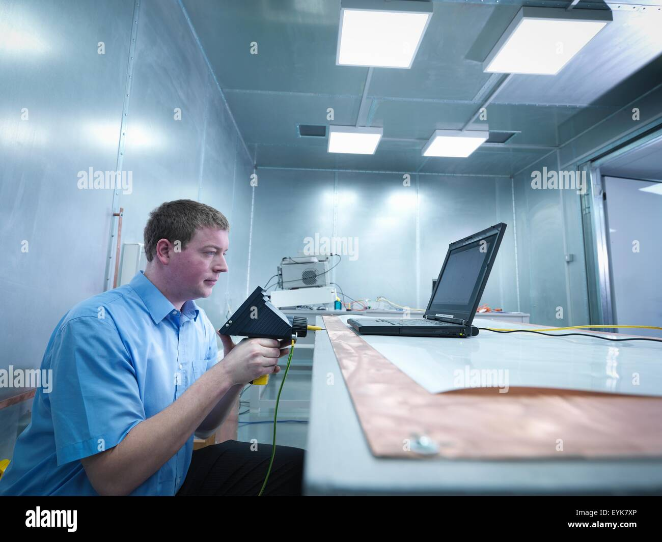 Engineer carrying out electro static discharge (ESD) testing using air discharge probe on copper table in screened - Stock Image