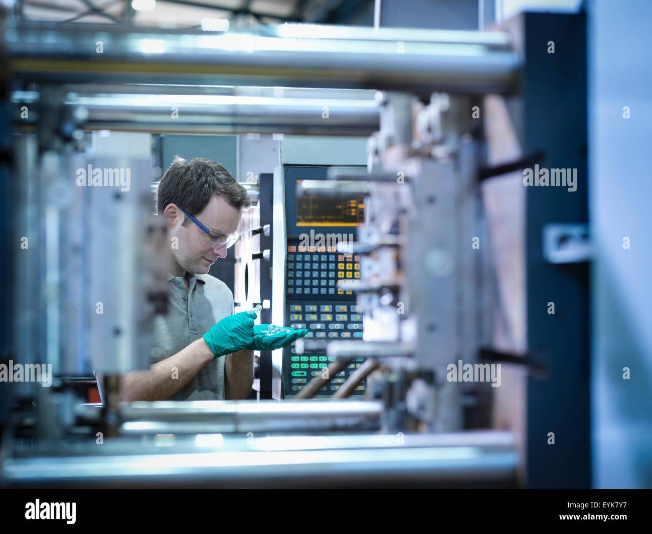 Worker inspecting parts from plastic injection moulding machine in plastics factory - Stock Image