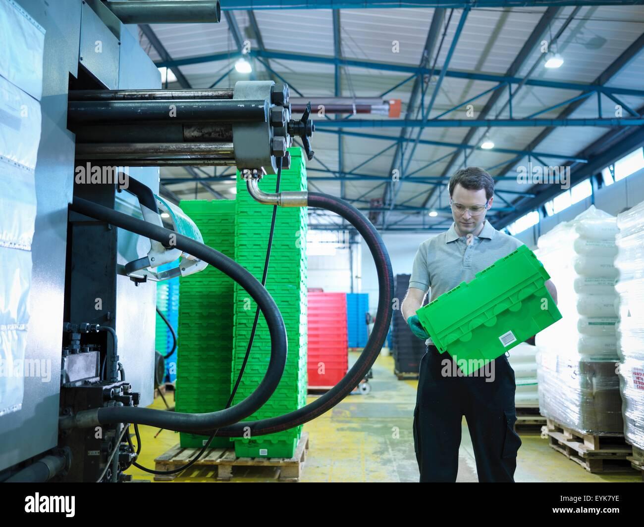 Worker inspecting plastic crates in plastics factory - Stock Image