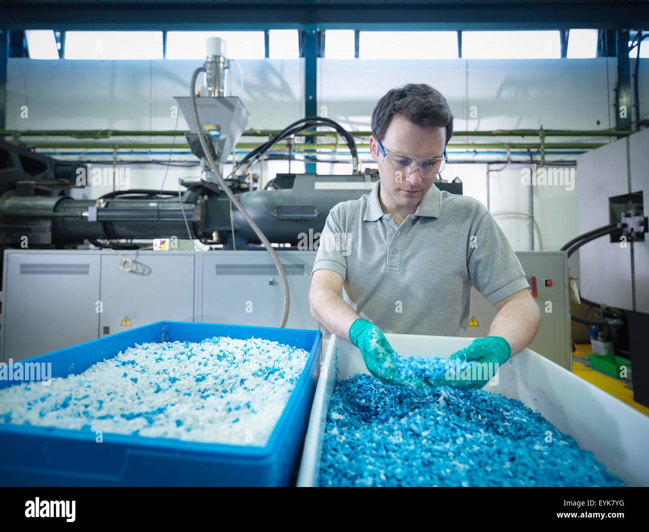Worker inspecting recycled plastic in plastics factory - Stock Image
