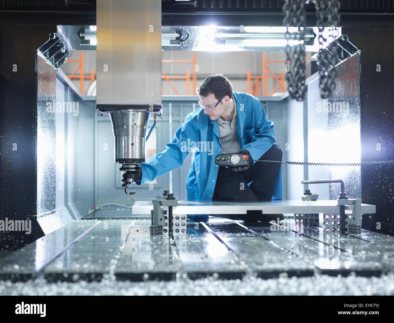 Worker in large CNC machine in plastics factory - Stock Image