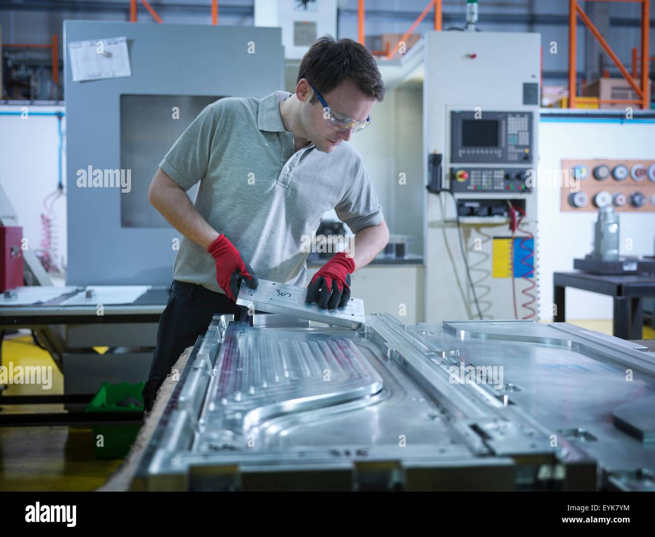 Worker inspecting part of mould in plastics factory - Stock Image