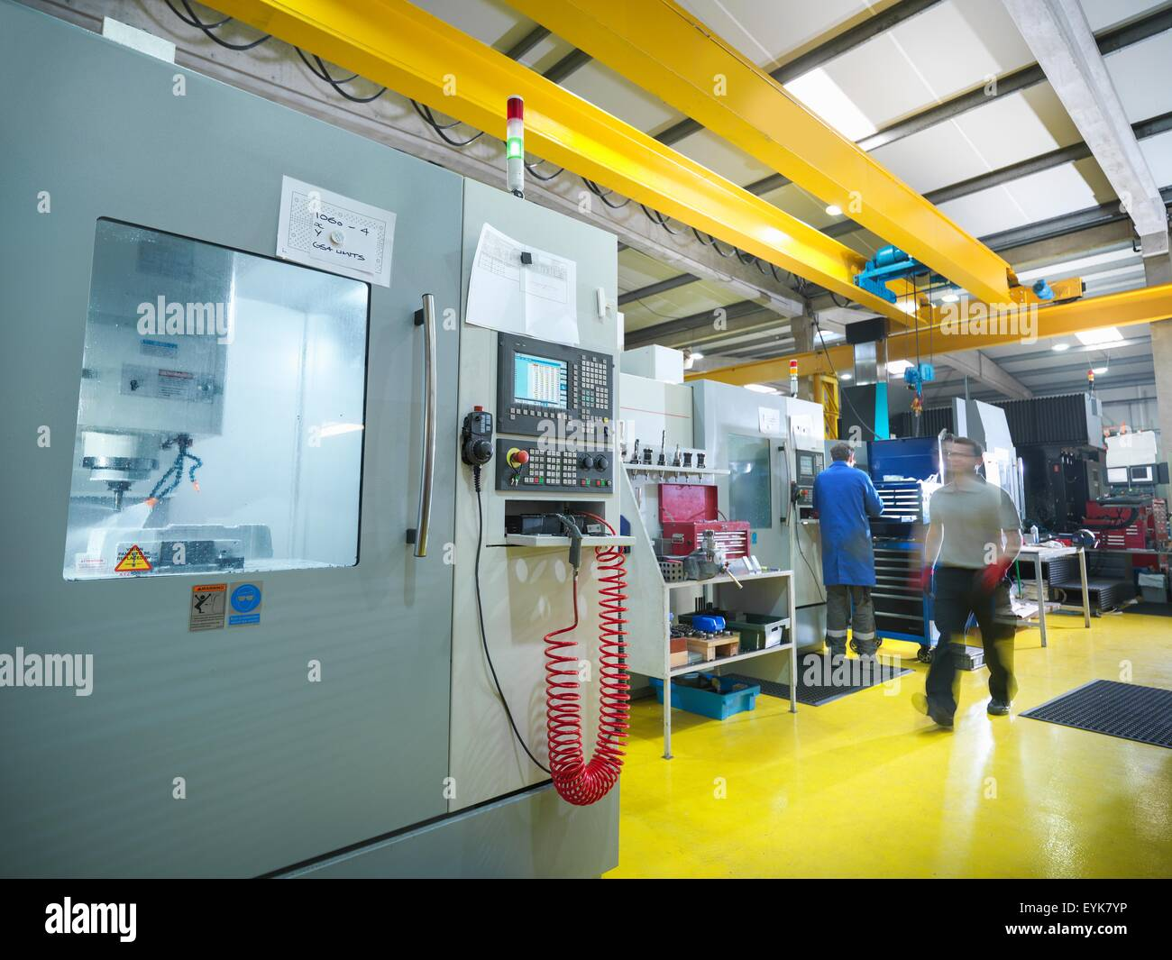 Workers with large CNC machine in plastics factory - Stock Image