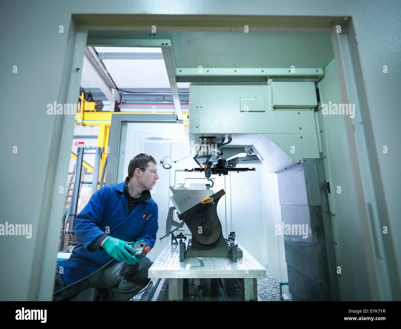 Worker using CNC machine in plastics factory - Stock Image