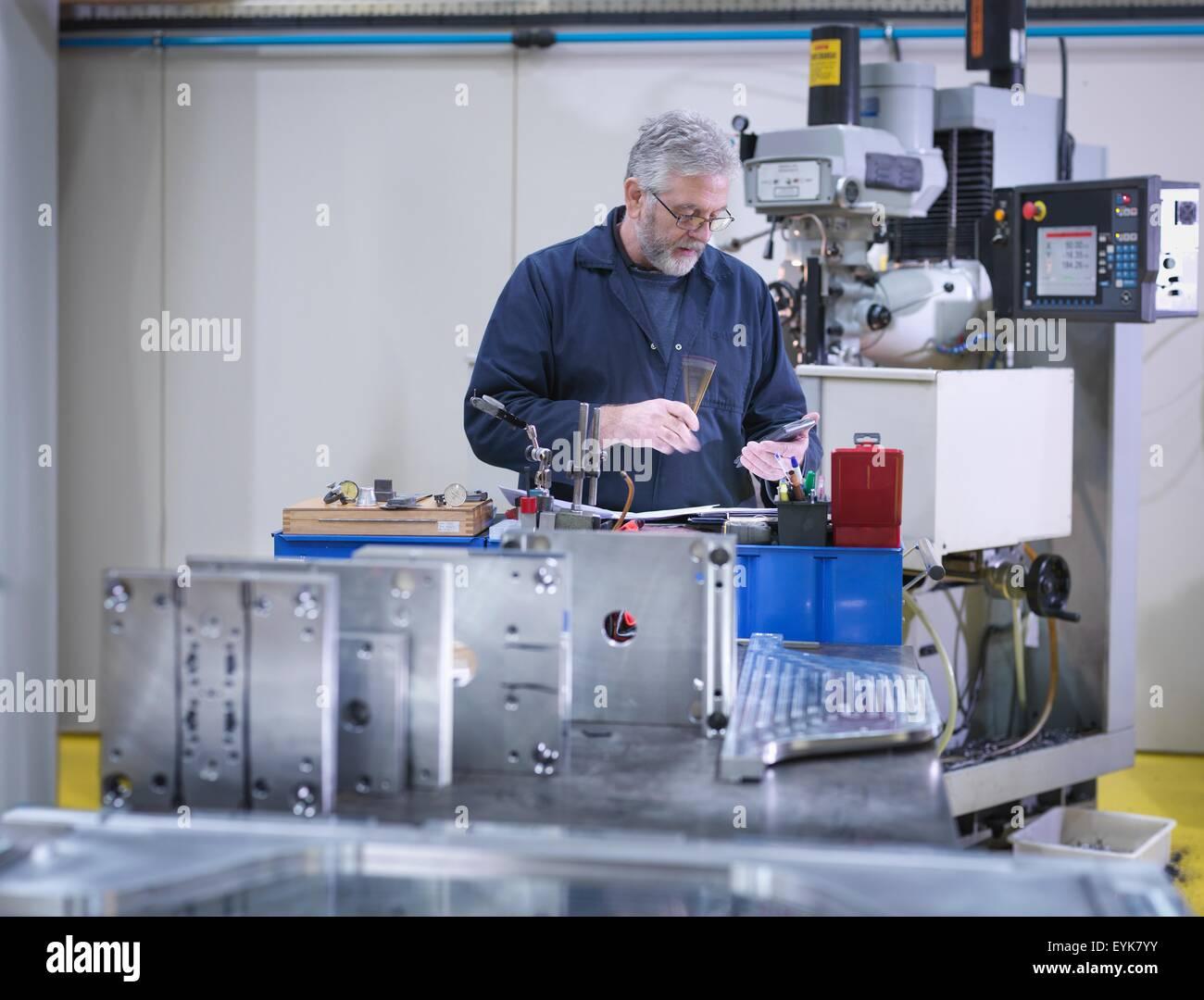 Mature engineer using lathe in engineering factor - Stock Image