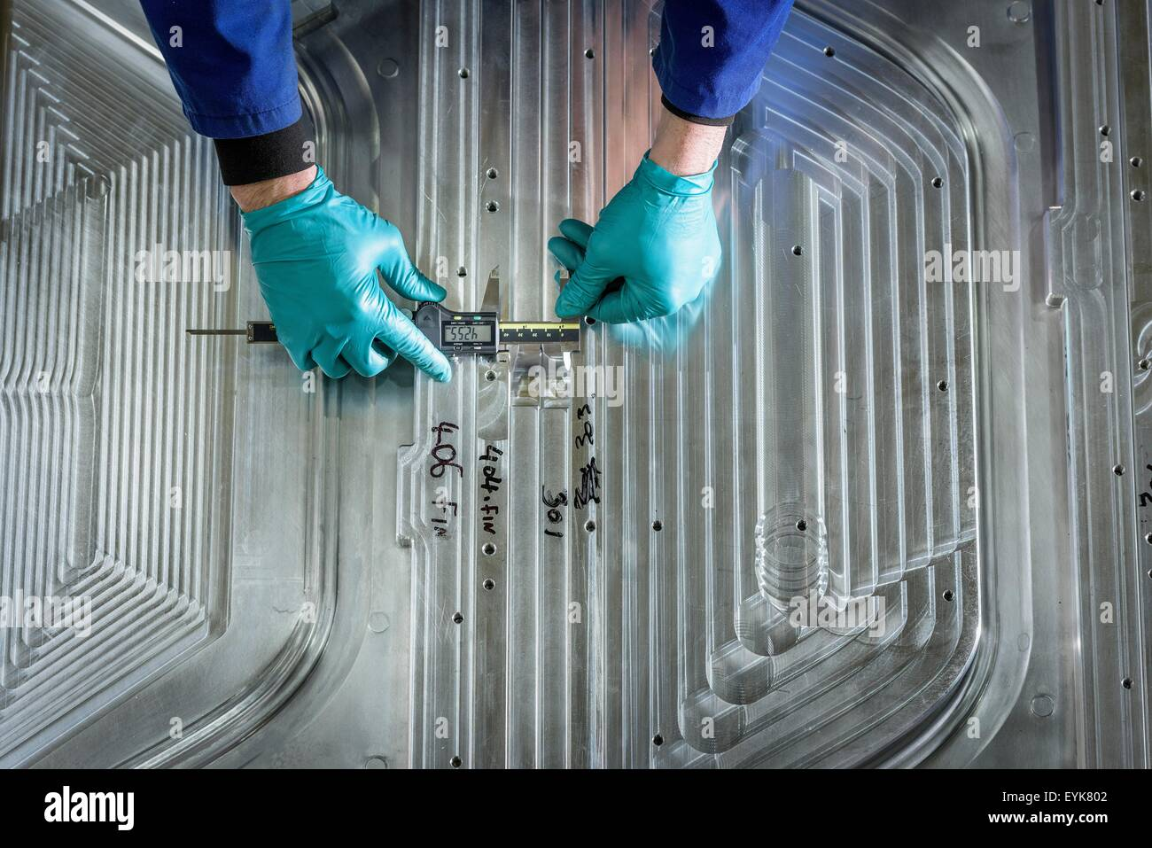 Overhead view of worker finishing metal mould in plastics factory, close up - Stock Image