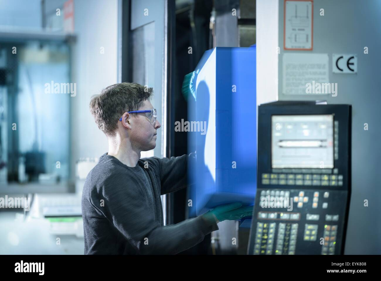 Worker removing plastic part from injection moulding machine in plastics factory - Stock Image