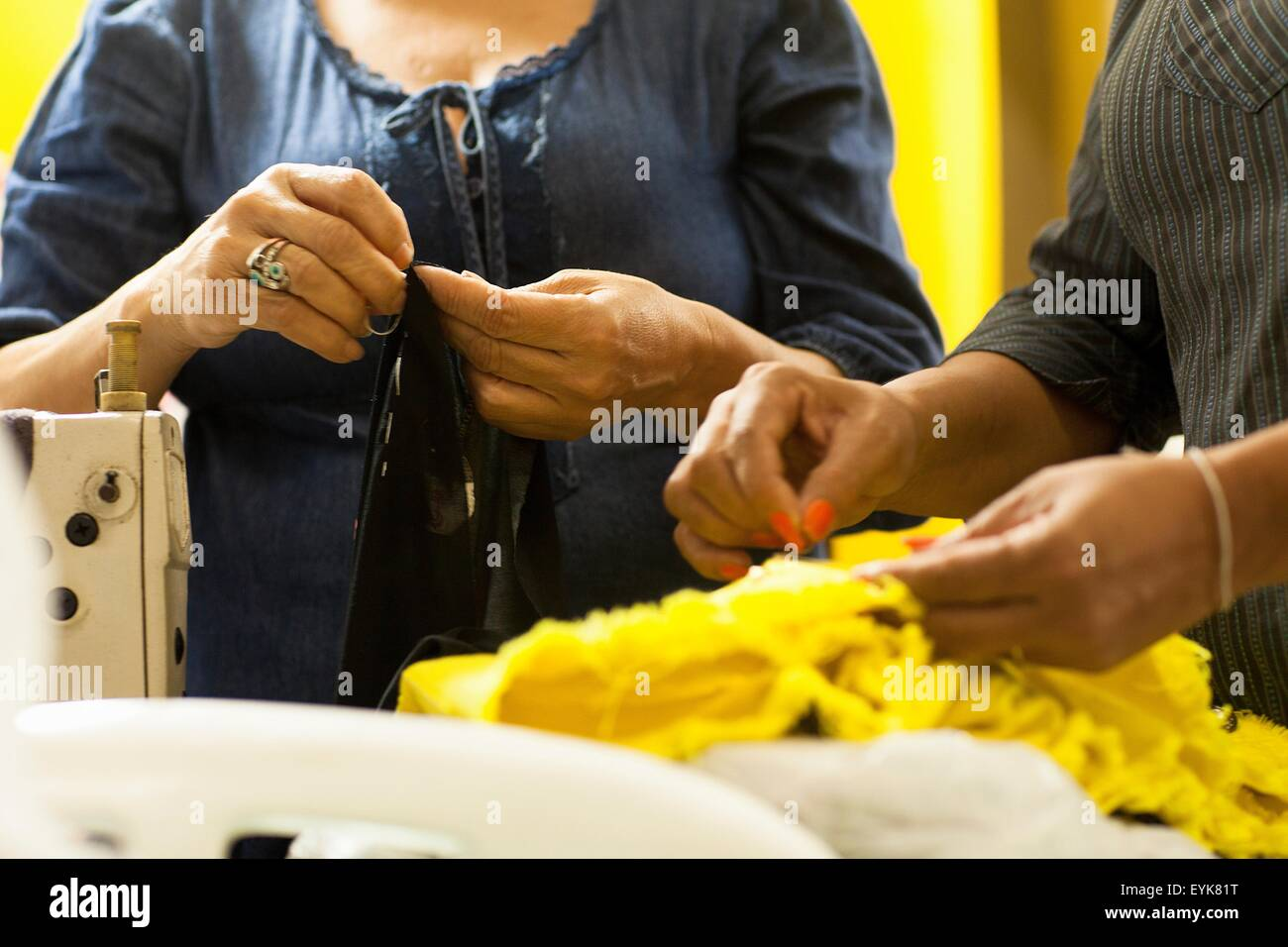 Cropped shot of two seamstresses sewing in workshop - Stock Image