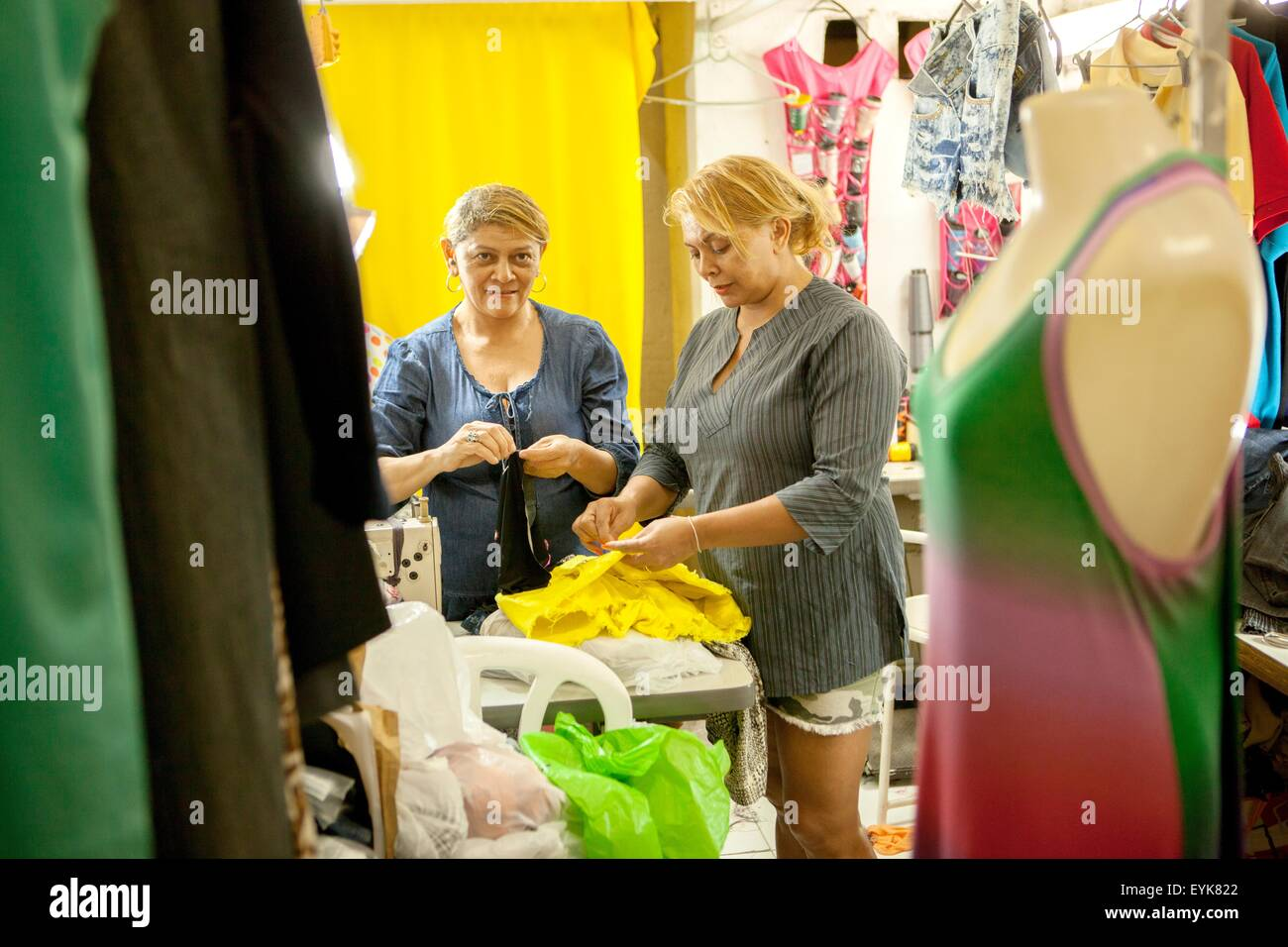 Two seamstresses preparing garments for sewing in workshop - Stock Image