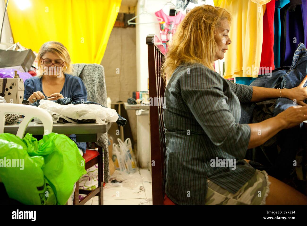 Two seamstresses working at sewing machines in workshop - Stock Image