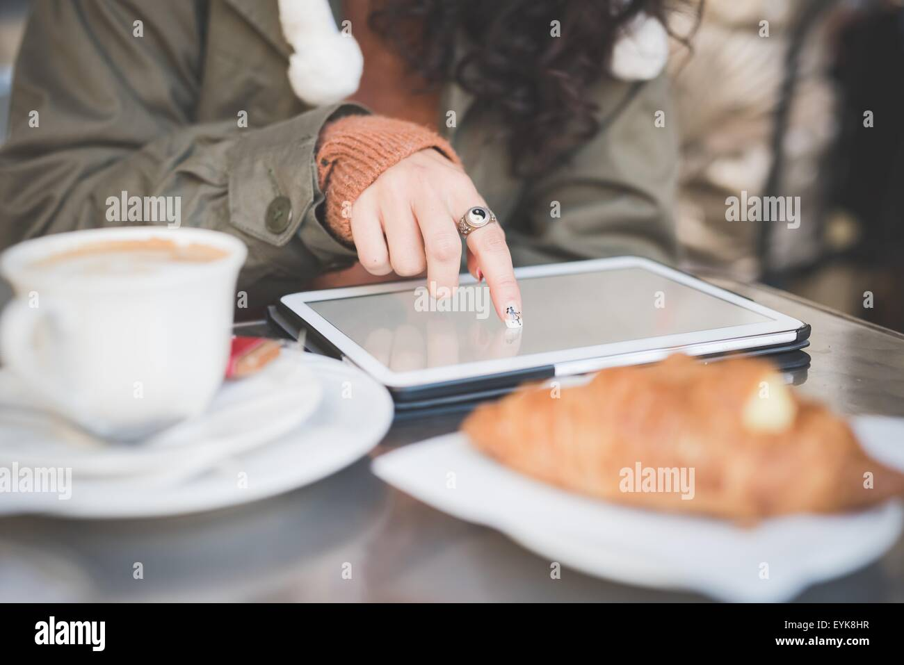Cropped shot of young woman using touchscreen on digital tablet at sidewalk cafe - Stock Image