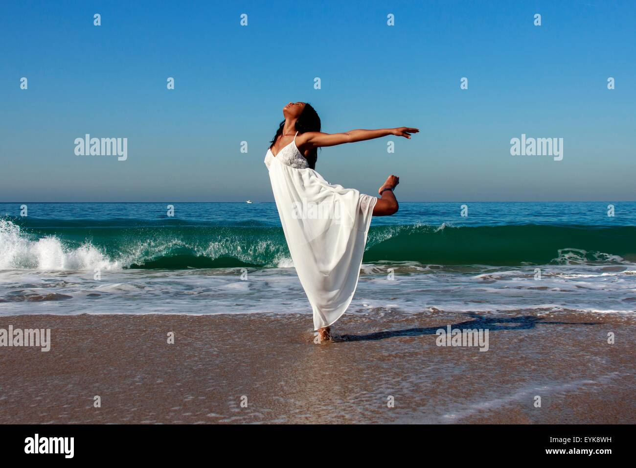 Young female dancer poised on one leg in ocean waves - Stock Image