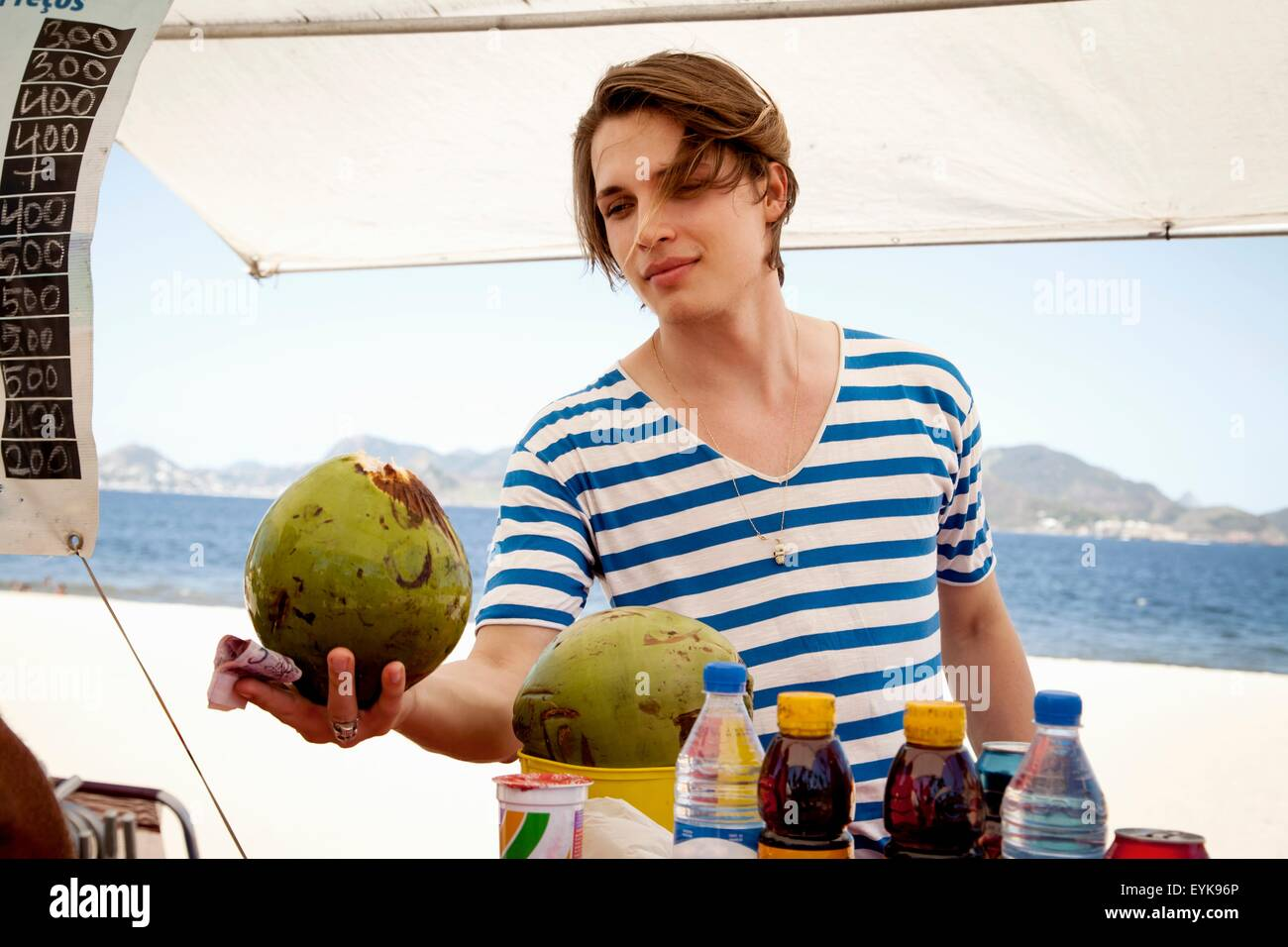 Young man buying coconut from kiosk - Stock Image