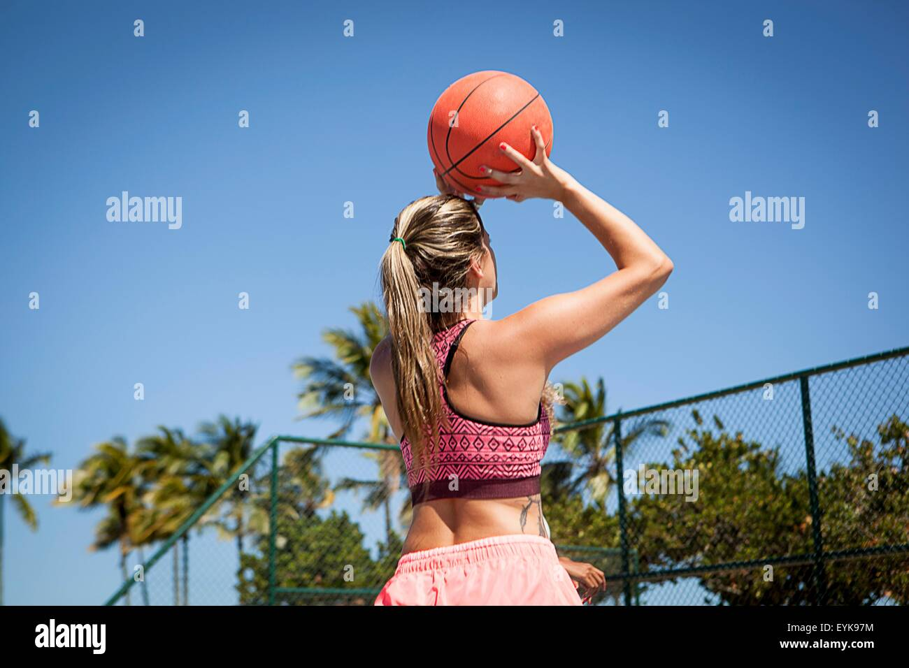 Young woman with basketball, about to take a shot, rear view - Stock Image