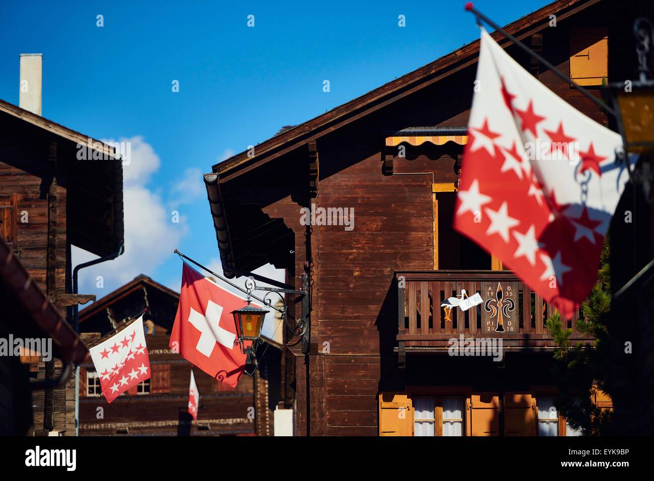 Flags on chalet buildings, Valais, Switzerland - Stock Image