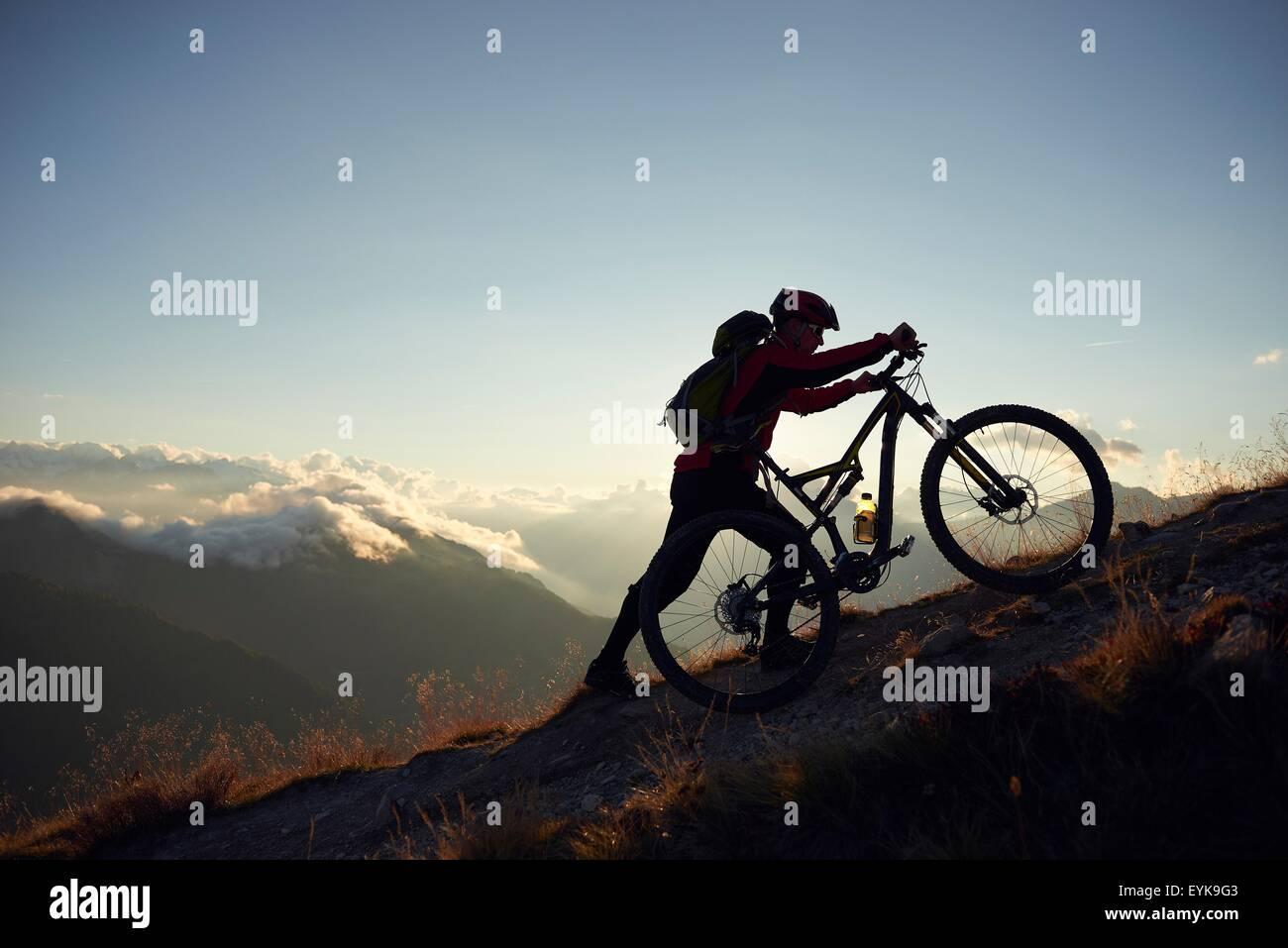 Mountain biker pushing bike uphill, Valais, Switzerland - Stock Image