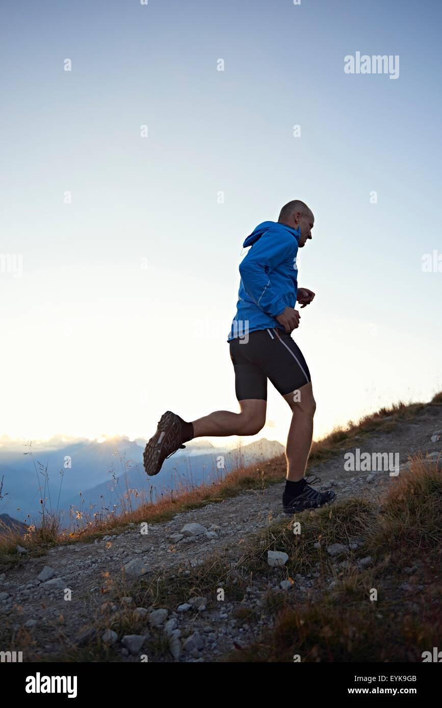 Trail runner running uphill, Valais, Switzerland - Stock Image