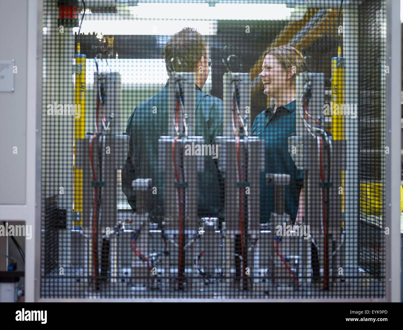 Workers in discussion on factory floor - Stock Image