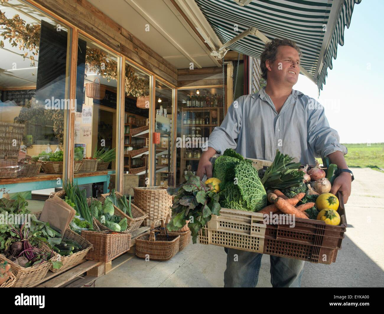 Portrait of male organic farmer with basket of organic vegetables outside farm shop - Stock Image