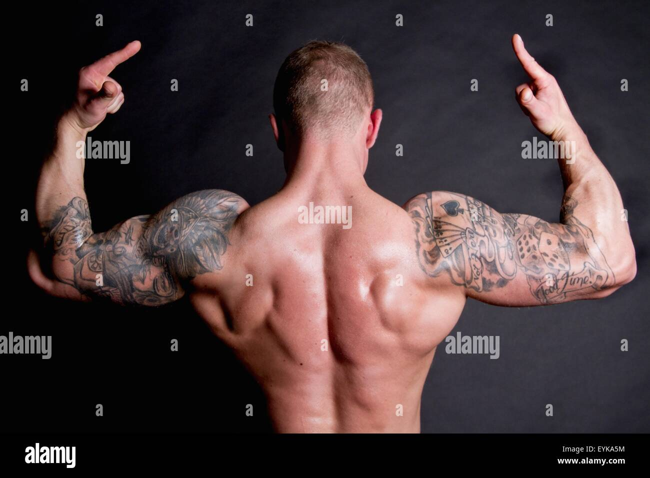 Young man showing rear double biceps - Stock Image