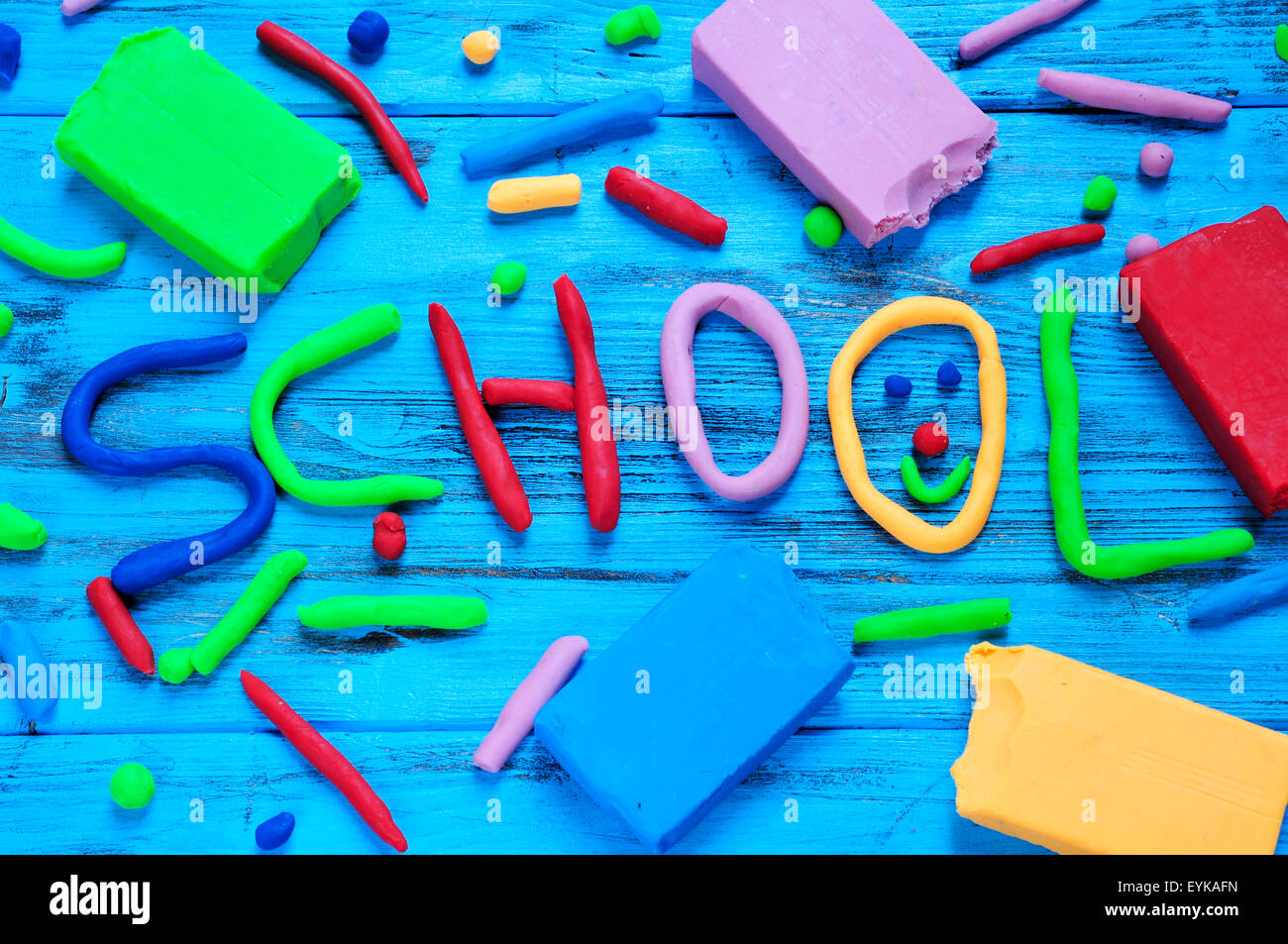 the word school written with modelling clay of different colors on a blue rustic wooden background - Stock Image