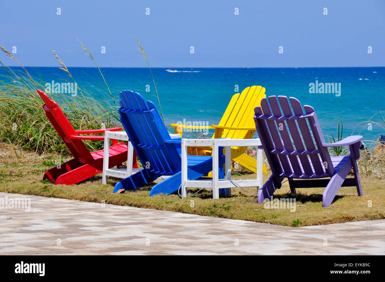 Four colorful Adirondack chairs overlooking the ocean and ...