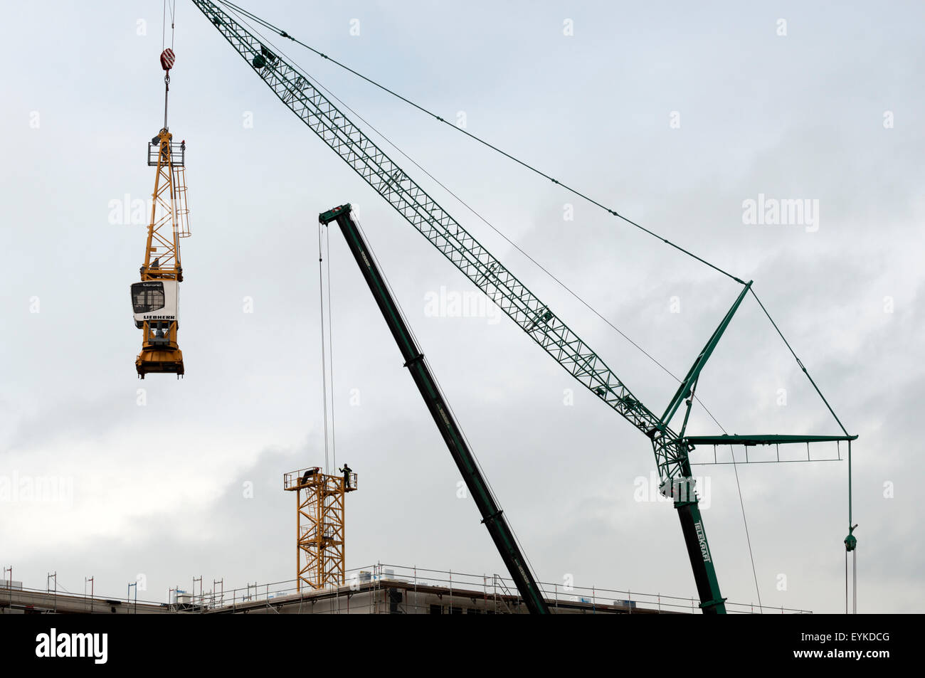 Construction workers dismantling tower crane - Stock Image