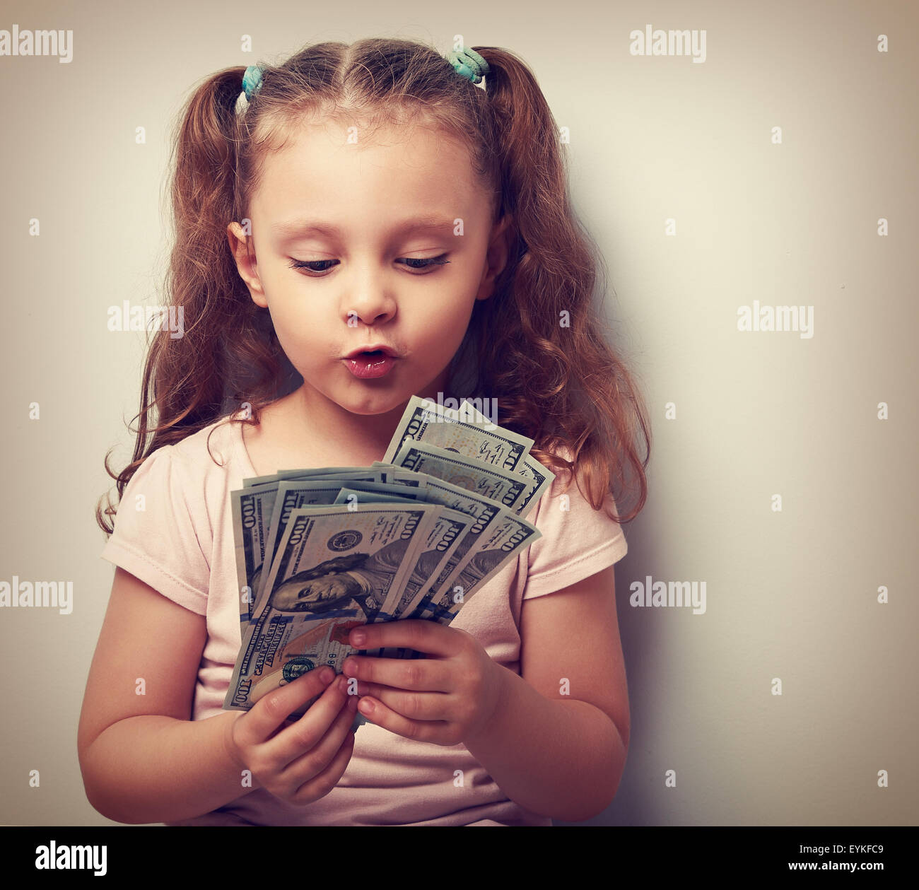 Fun grimacing kid girl looking and counting money in the hands. Vintage closeup portrait - Stock Image